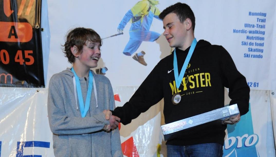 Deux jeunes participants sur le podium qui se serrent la main.